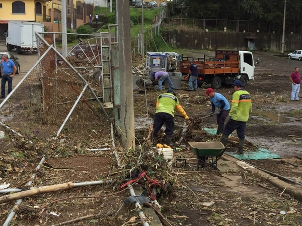 Empleados municipales limpian el terreno que se inundó la tarde de este martes en Barrio Luján. En ese sitio el agua arrastró carros y un camión cisterna de Dos Pinos.