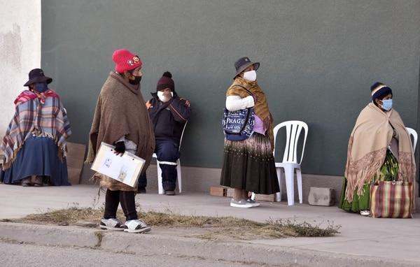 Mujeres indígenas bolivianas hacían fila fuera de una oficina bancaria en la ciudad de El Alto para retirar un bono de $71 que les da el Estado como auxilio ante la crisis del nuevo coronavirus,