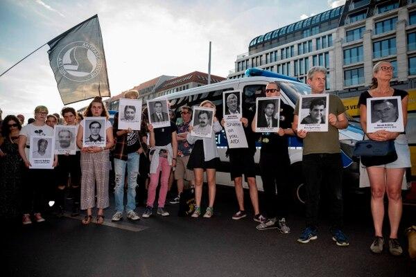 Manifestantes muestran fotografías de personas que fallecieron durante actos de violencia propiciados por la extrema derecha ante el asesinato de Walter Luebcke. Foto: AFP