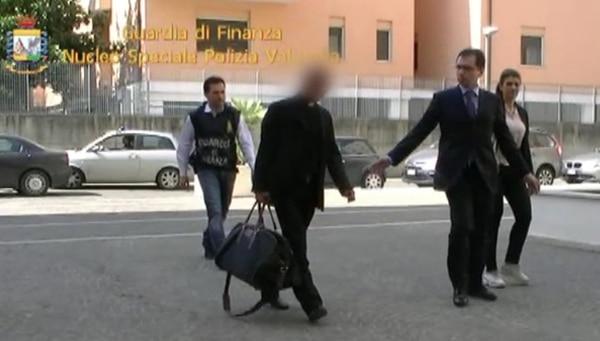 Agentes de la Guardia de Finanzas escoltan a monseñor Nunzio Scarano, inmediatamente después de detenerlo en Roma. | AFP