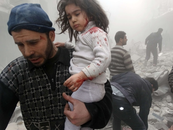 Un hombre rescata a una niña hallada ayer entre los escombros de un edificio destruido por explosivos lanzados desde helicópteros en Alepo. | AFP