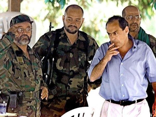 El entonces comisionado de paz del Gobierno de Colombia, Camilo Gómez (de civil), y el desaparecido cabecilla de las FARC, Raúl Reyes (izq.), en la última oportunidad que las partes dialogaron, en febrero del 2002.   AFP