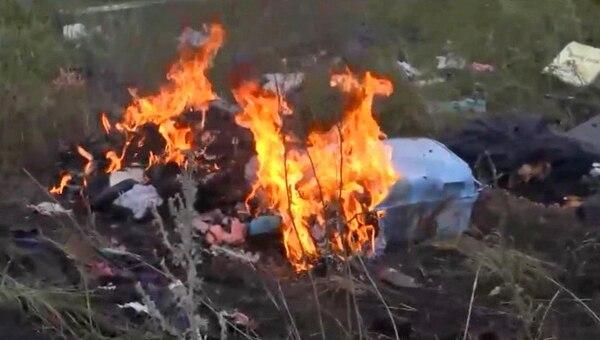 Restos del equipaje del vuelo derribado en Ucrania arden tras la caída del avión.