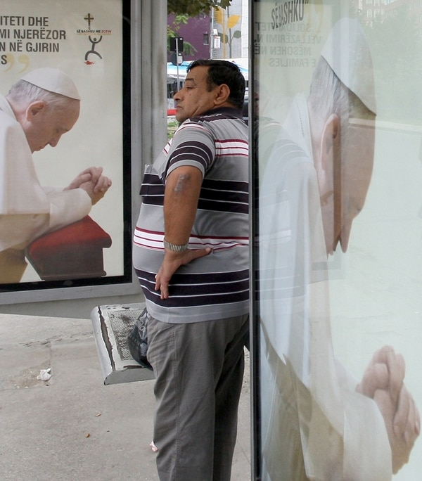 Un hombre estuvo ayer junto a un cartel del Papa en Albania. | AFP