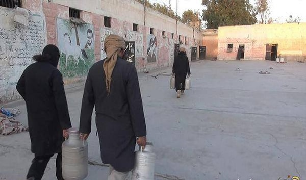 Militantes del Estado Islámico transportaban envases plásticos con con combustible mientras se preparaban para destruir la prisión en la ciudad de Palmira, Siria.