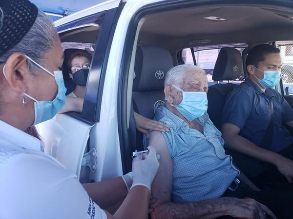 Noé Segura Artavia, de 102 años, recibió la vacuna la mañana de este martes en el área de salud de Ciudad Quesada sin necesidad de salir del carro que lo transportaba. Thais Ching Zamora, directora del Área, le aplicó la inyección. Foto: Cortesía Área de Salud de Ciudad Quesada
