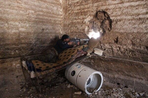 Un combatiente rebelde apunta con su rifle detrás de una pared. La guerra en Siria ha cobrado por tres años más de 150.000 vidas.