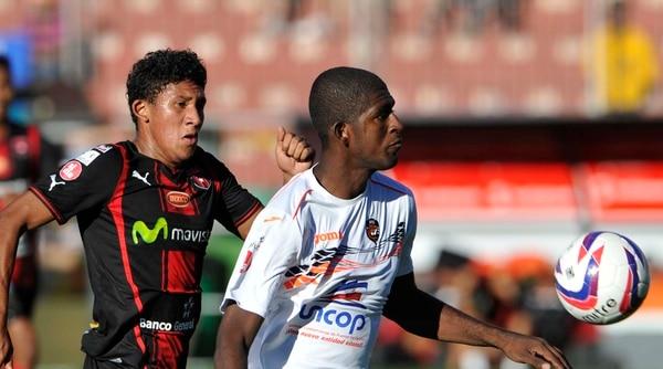 José Guillermo Ortiz, de Alajuelense, busca quitarle la pelota a Yamir Vergara de Puntarenas.