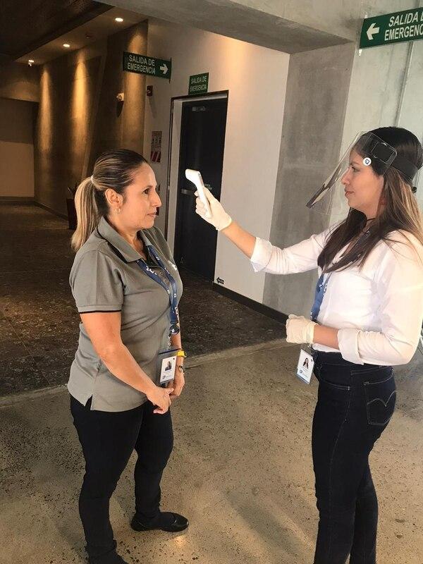 Parte del protocolo sanitario de Portafolio Inmobiliario para poder realizar trabajo presencial es que los colaboradores se tomen la temperatura al entrar al edificio. En la fotografía Yessenia Chavarría (gris) y Jenny Chaves. Fotografía: Cortesía.