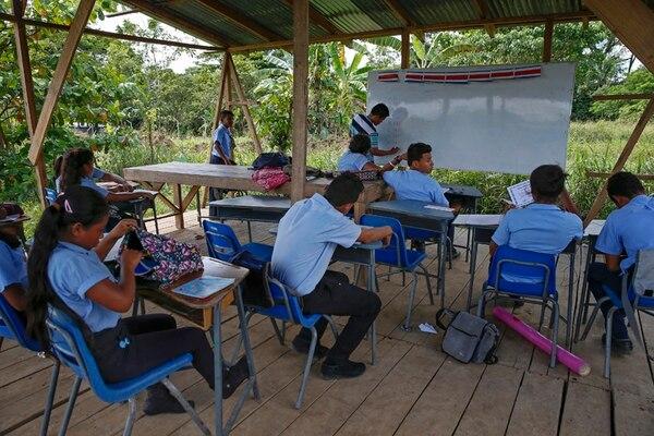 Alumnos del liceo de Shiroles reciben clases en un aula sin paredes. (Izq) Farlen Artavia (izq), Wendy Aguilar y Junior García, del liceo Palmera, de regreso a sus casas.   MAYELA LÓPEZ