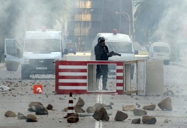 Un policía antimotines sostenía un arma en las calles de Túnez, en medio de las revueltas que cobraron varias vidas. Tras un mes de violencia el presidente Zine El Abidine Ben Alí abandonó ayer el país. | AP