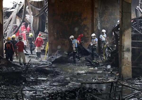 Equipos de rescate inspeccionan fábrica de zapatos afectada por incendio en Valenzuela, al este de Manila (Filipinas).