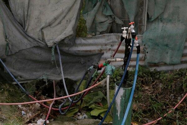 En el precario Martina Bustos en Liberia, los vecinos deben conectar mangueras a tubos públicos para llevar agua a sus casas. | ALBERT MARÍN
