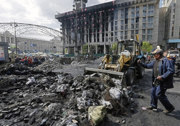 Trabajadores ucranianos quitan una barricada cerca de la Plaza de la Independencia de Kiev, Ucrania, el 23 de abril del 2014. La Cancillería ucraniana acusa a Rusia de boicotear el cumplimiento de los acuerdos de Ginebra, que penden de un hilo por la negativa de las milicias prorrusas a deponer las armas y desalojar los edificios gubernamentales.