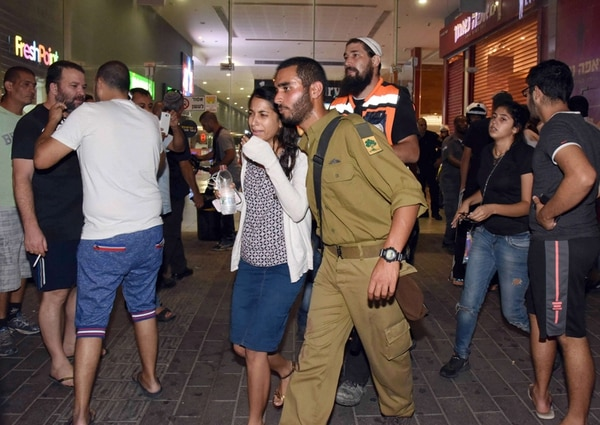 Una joven iba acompañada este lunes en la estación de autobuses de la ciudad israelí de Beer Sheva, después de que un hombre atacó con un arma de fuego allí y mató a una persona.   AFP