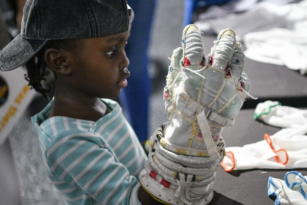 A young attendee tries on a glove from a spacesuit during the Apollo 11, 50th anniversary celebration at Space Center Houston on July 20, 2019, in Houston, Texas. (Photo by Loren ELLIOTT / AFP)