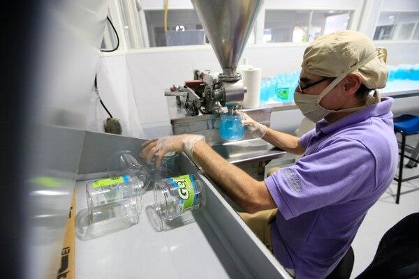 Kristian Fonseca trabaja en el laboratorio de la empresa. En la imagen, llena los envases con gel para cabello. Fotografía: Rafael Pacheco.