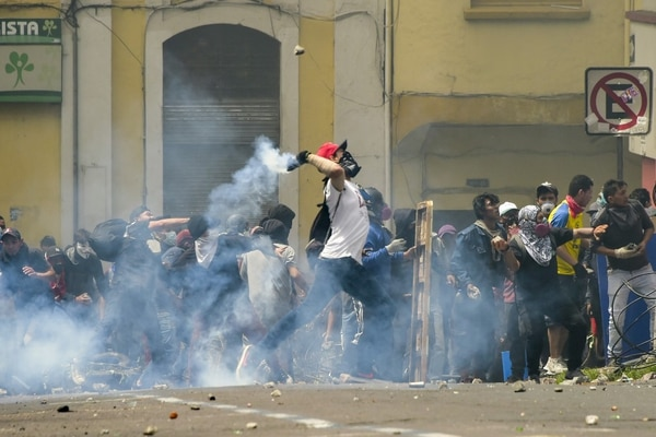 Manifestantes protestan frente a una barricada en llamas durante los enfrentamientos con la Policía antidisturbios, en Quito, (Photo by RODRIGO BUENDIA / AFP)