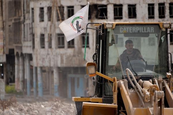 Un trabajador de las fuerzas militares utiliza una excavadora para limpiar los escombros en la ciudad vieja del norte de Mosul, en Irak, el 6 de abril del 2021. Foto: AFP