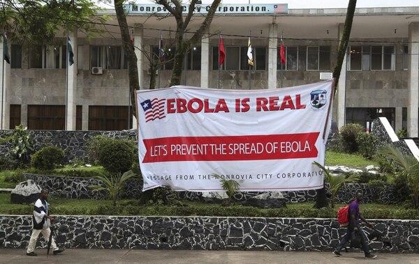Dos liberianos caminan por delante de un cartel en el Ayuntamiento de Monrovia, en Liberia. El Gobierno ordenó cerrar todas las escuelas del país hasta nueva orden y declaró un
