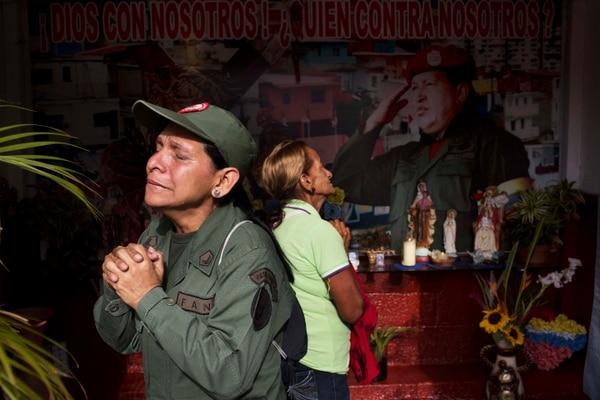 Marisol Pérez, especialista del Ejército de Venezuela, llora durante su visita a una capilla cerca de Mausoleo del fallecido presidente de Venezuela, Hugo Chávez, en Caracas, este miércoles.