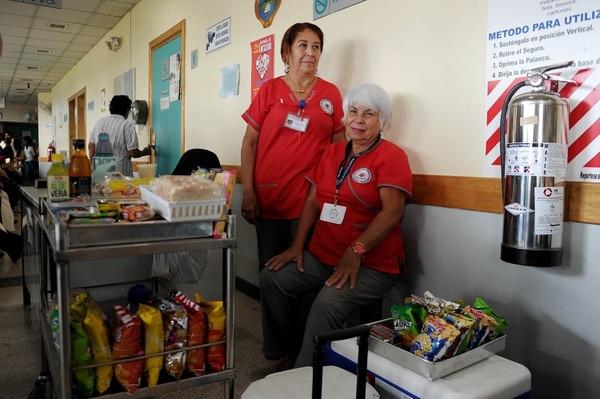 Los ingresos que se recaudan en estos puestos de comida de la Asociación Pro Cuidado Paliativo permiten comprar medicinas y otros insumos para pacientes muy pobres. Esto se logra con la ayuda de voluntarias como Olga Acuña (izq.) y Antonieta Loáiciga.