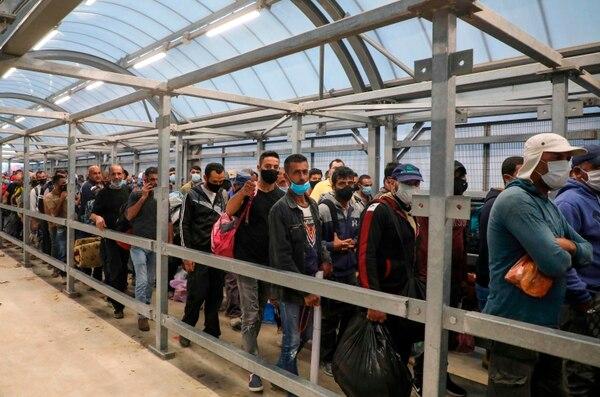 Trabajadores palestinos hacían fila, este domingo 28 de junio del 2020, en un puesto de control israelí para poder ingresar a la ciudad de Hebrón,en Cisjordania, sometida a ocupación por parte del Estado hebreo.