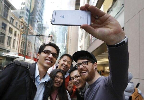 Un empleado de Apple posa para un 'selfie' con varios clientes con un iPhone 6S.