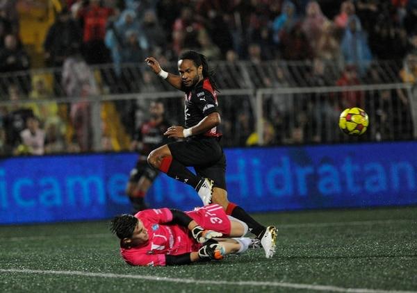 Jonathan McDonald lucha por el balón con el guardameta universitario Luis Alpízar.