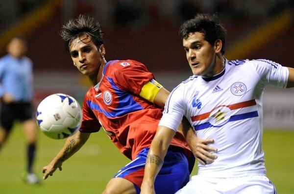 Bryan Ruiz (derecha), capitán de la Tricolor, disputa el balón con el paraguayo Gustavo Raúl Gómez durante el partido amistoso en el Estadio Nacional rumbo al Mundial de Brasil 2014.