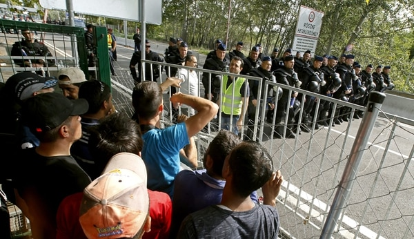 La policía húngara bloqueó este martes una calle que conecta la frontera del país con Serbia, ante la mirada de migrantes en Röszke. Hungría declaró un estado de emergencia en dos condados del país que hacen frontera con Serbia a raíz de la crisis migratoria, acción que abre camino para reforzar la presencia de la policía a lo largo de la frontera. | EFE