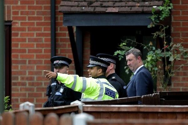 Un agente policial conversaba este domingo 17 de setiembre del 2017 con otros colegas durante una inspección forense que se hizo a un vivienda en el barrio residencial de Sunbury-on-Thame, 20 kilómetros al suroeste de Londres.