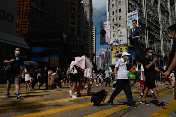 Peatones usan máscaras faciales mientras cruzan una carretera, en Hong Kong, el 29 de julio del 2020. Foto: AFP