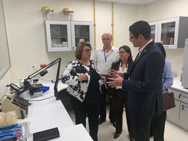 María Teresa Acuña, directora del Laboratorio de Inocuidad Microbiológica de Alimentos, le muestra las instalaciones a Daniel Salas, ministro de Salud, a la viceministra Alejandra Acuña y a otras autoridades del ministerio. Fotografía: Jorge Castillo
