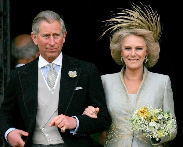 En esta imagen de archivo, tomada el 9 de abril del 2005, el príncipe Carlos de Inglaterra y su esposa Camila, duquesa de Cornualles, posan a la salida de la capilla de San Jorge en Windsor, Inglatera, tras la bendición religiosa de su enlace civil. (Foto AP/ Alastair Grant, archivo)