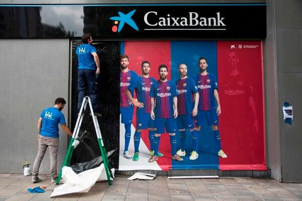 Dos hombres colocaron este miércoles un nuevo cartel fuera del Camp Nou, en Barcelona. El cartel anterior incluía al delantero brasileño Neymar, quien en los próximos días sería presentado con el París Saint Germain.