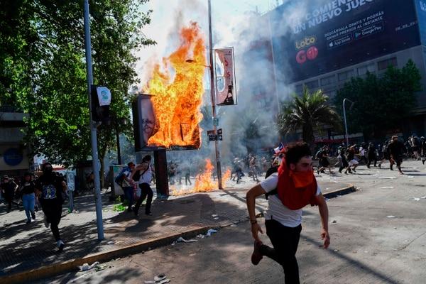 Manifestantes incendian vallas publicitarias, en Santiago, el 21 de octubre del 2019. Foto: AFP
