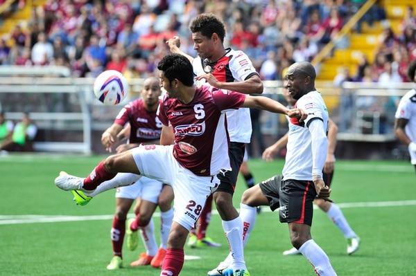 Josué Martínez (28) pelea el balón con Armando Alonso. En Alajuelense dicen estar seguros de que le darán vuelta al 1-0 de la ida. | ALEXÁNDER OTÁROLA