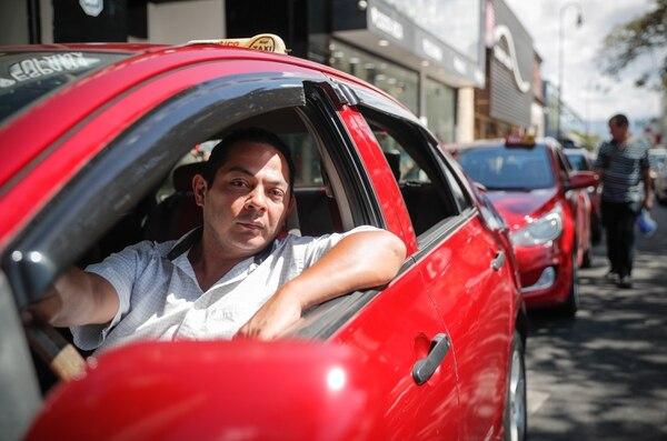 El taxista Michael Segura asegura que la baja presencia de trabajadores en San José por la emergencia nacional le provoca una afectación a su bolsillo, pues los ingresos mermaron desde entonces. Fotografía: Jeffrey Zamora.