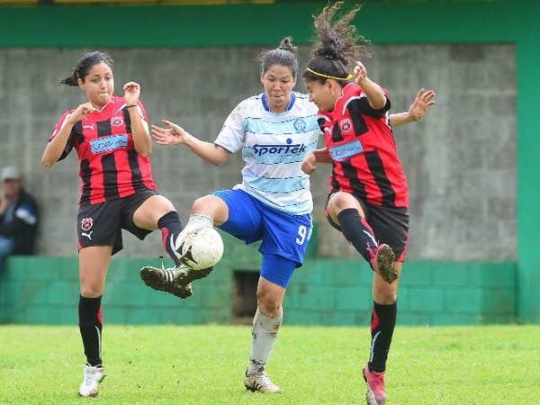 Marilín Solano (de blanco) disputa el balón entre dos defensoras de UCEM, en el encuentro de ayer en el estadio de San Joaquín de Flores, en Heredia. Solano fue la anotadora del único tanto de las heredianas. | RAFAEL PACHECO.