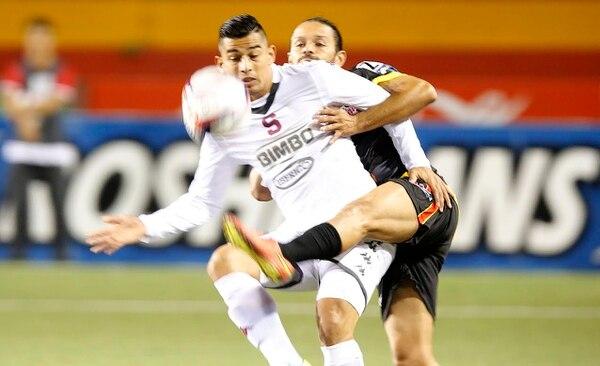 El atacante morado Ariel Rodrúguez (de blanco) protege el balón ante la marca de un jugador belemita.