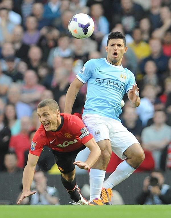 Sergio Agüero (celeste) marcó dos de los cuatro goles del Manchester City. Acá supera al defensor Nemanja Vidic del Manchester United. | EFE