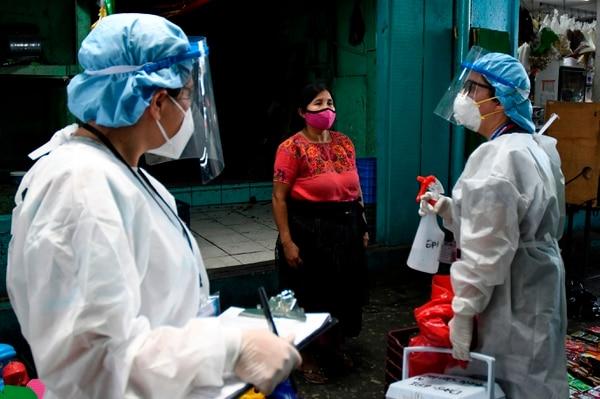 Trabajadores de la salud se preparan para realizar pruebas de coronavirus en un mercado en la ciudad de Guatemala, el 21 de mayo del 2020. Foto: AFP