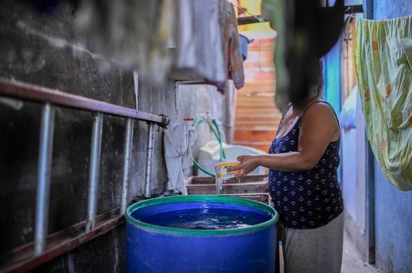 Hania Naranjo llena un estañón con agua cada mañana. Lo usa para lavar platos y cargar el tanque del servicio sanitario. | JOSÉ CORDERO.