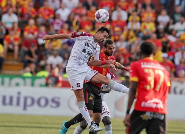 Mariano Torres lucha por un balón aéreo con Yendrick Ruiz en el juego ante Herediano. Fotografía: John Durán