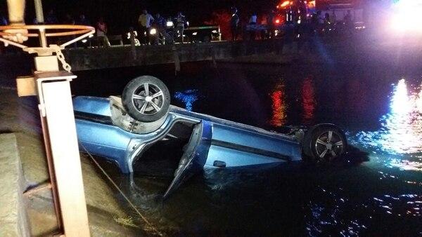 El automóvil sedán Mitsubishi fue extraído del canal con la ayuda de varias cadenas. El conductor de este permanece desaparecido. Foto: Julio Segura