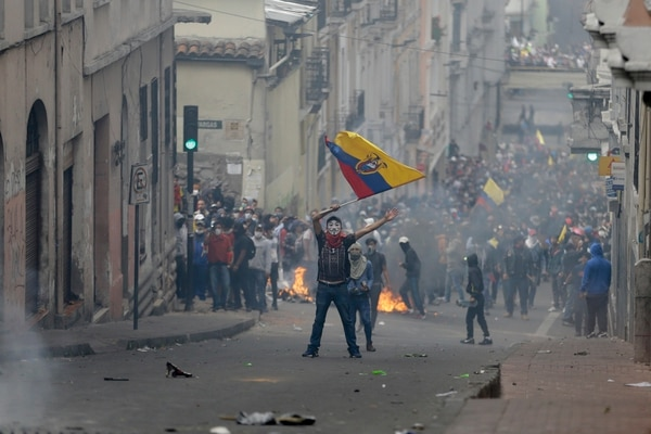 A protester waves an Ecuadorean national flag during clashes in downtown Quito, Ecuador, Wednesday, Oct. 9, 2019. Protests, which began when Moreno's decision to cut subsidies led to a sharp increase in fuel prices, have persisted for days. (AP Photo/Fernando Vergara)