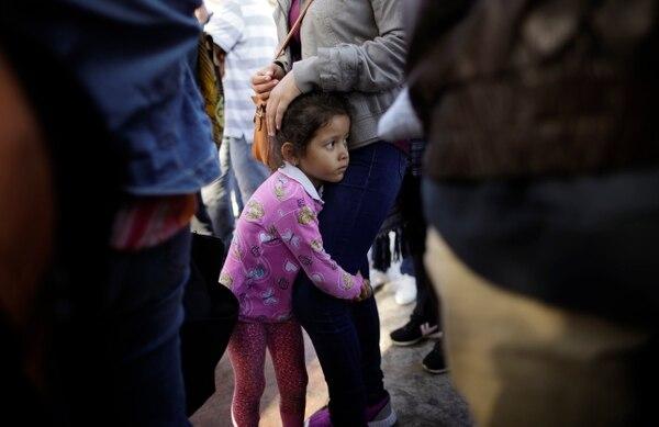 Nicole Hernández se aferra a su madre mientras esperan para pedir asilo político en Estados Unidos, al otro lado de la frontera en Tijuana, México, el miércoles 13 de junio de 2018. La familia ha estado esperando alrededor de una semana en esta ciudad fronteriza con la esperanza de escapar de la violencia en su estado natal, Guerrero.