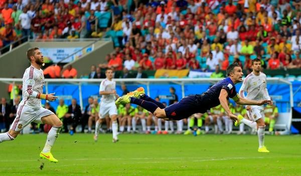 Robin van Persie vuela y anota de cabeza el golazo del empate holandés, mientras Ramos y Piqué no pueden más que mirar. Era el 1-1 y nadie imaginaba la paliza naranja que vendría en el segundo tiempo. | AP