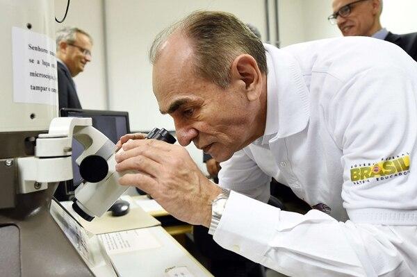 El ministro de Salud brasileño Marcelo Castro observa el virus del Zika por un microscopio.   AFP